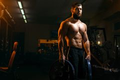 Bodybuilder in the gym exercising barbell royalty free stock image