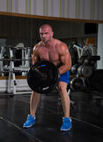 Bodybuilder in the gym. Muscular man exercising with weights. He is performing T bar rows for back muscle Royalty Free Stock Images