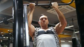 Bodybuilder in the gym performs pull up for biceps with metal chain stock video