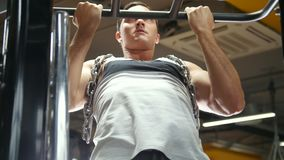 Bodybuilder in the gym performs pull up for biceps with metal chain stock video footage
