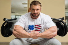 Bodybuilder in gym. Sportsman sitting at trainers. Mirror on the wall in gym royalty free stock image