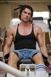 Bodybuilder in gym working out on legs machine Royalty Free Stock Images