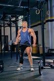 Bodybuilder hält geeigneten Hammer des Kreuzes Stockbild