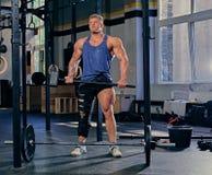 Bodybuilder hält geeigneten Hammer des Kreuzes Stockfotos