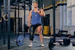 Bodybuilder hält geeigneten Hammer des Kreuzes Lizenzfreie Stockbilder