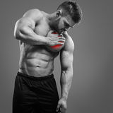 Bodybuilder Heart pain. Muscular shirtless man with heart pain over gray background. Concept with highlighted glowing red spot royalty free stock photo