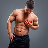 Bodybuilder Heart pain. Muscular shirtless man with heart pain over gray background. Concept with highlighted glowing red spot stock image