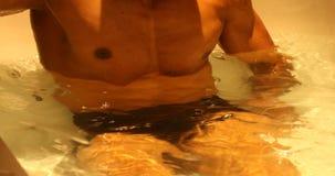 Bodybuilder het baden in de badkamers stock video