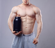 Bodybuilder holding a black plastic jar with whey. Protein on grey background. Without face Royalty Free Stock Photos
