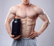 Bodybuilder holding a black plastic jar with whey protein on grey background. Without face Royalty Free Stock Photo