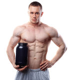 Bodybuilder holding a black plastic jar with whey. Protein isolated on white background Stock Photos