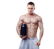 Bodybuilder holding a black plastic jar with whey. Protein isolated on white background Royalty Free Stock Image