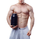 Bodybuilder holding a black plastic jar with whey protein on white background. No face.  Royalty Free Stock Photography
