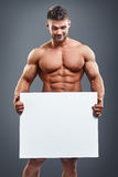 Bodybuilder holding blank white poster Stock Image