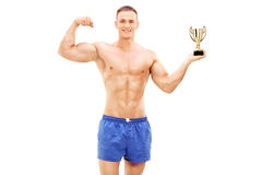 Bodybuilder holding a golden trophy Stock Photo