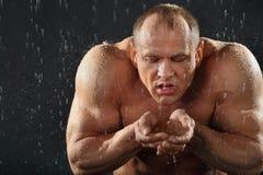 Bodybuilder im Regen trinkt Wasser von den Händen Stockfotografie