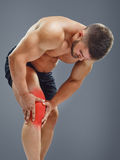Bodybuilder Knee pain. Sportsman holding hands on a sick knee, isolated on gray background. Glowing red spot concept royalty free stock photography