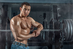 Bodybuilder leaned on the machine. Stock Photography