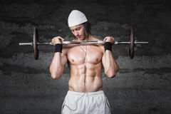 Bodybuilder lifiting weigths. Muscle bodybuilder lifiting weigths while listening to music Stock Image