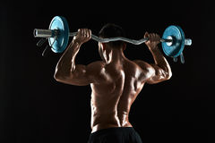 Bodybuilder lifting a barbell on black background Stock Photography
