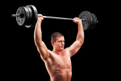 Bodybuilder lifting a heavy weight. On black background Royalty Free Stock Photos