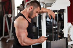 Bodybuilder looking at his phone Stock Photo