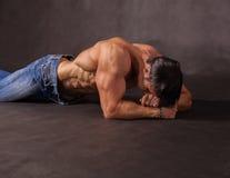 Bodybuilder lying on the floor in the studio Stock Photo