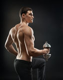 Bodybuilder makes exercise with dumbbells Stock Image