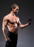 Bodybuilder man with a bottle of sport supplements Royalty Free Stock Photos