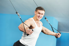 Bodybuilder man doing exercises in fitness club. Smiling athlete bodybuilder man doing muscles exercises at weight machine in fitness sport club gym Royalty Free Stock Photo