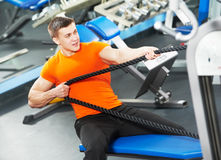Bodybuilder man doing exercises in fitness club. Smiling athlete bodybuilder man doing muscles exercises at weight machine in fitness sport club gym Royalty Free Stock Image