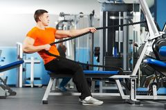 Bodybuilder man doing exercises in fitness club. Smiling athlete bodybuilder man doing muscles exercises at weight machine in fitness sport club gym Stock Photo