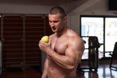Bodybuilder Man Eating An Apple Royalty Free Stock Photo