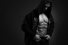 Bodybuilder man in the hood showing his torso Royalty Free Stock Image