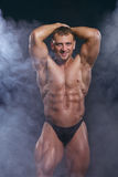 Bodybuilder man with a perfect muscle body on dark with smoke Royalty Free Stock Photo