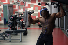 Bodybuilder man posing in the gym. Muscular black man posing in gym, shaped abdominal. Strong male naked torso abs, working out Royalty Free Stock Image