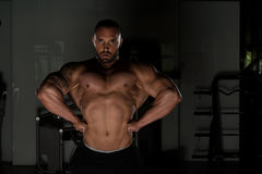 Bodybuilder Man Posing In The Gym. Man Standing Strong In The Gym And Flexing Muscles - Muscular Athletic Bodybuilder Fitness Model Posing After Exercises Stock Photography