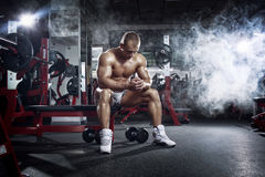 Bodybuilder man relaxing after workout in the gym Stock Image