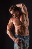 Bodybuilder man. Shirtless bodybuilder man posing for photographer in photo studio. Ideal man in blue jeans demonstrating his biceps, abs, torso etc Royalty Free Stock Photography