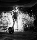 Bodybuilder man standing with barbell, workout in gym Royalty Free Stock Photo
