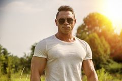 Bodybuilder man standing in lawn stock photo