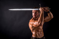 Bodybuilder man with a sword. Bodybuilder man posing with a sword isolated on black background. Serious shirtless man demonstrating his mascular body Stock Photography