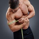 Bodybuilder measuring biceps with tape measure. Closeup Muscular bodybuilder measuring biceps with tape measure isolated over gray background. Bodybuilder tries stock photo