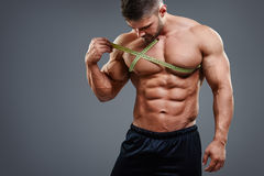 Bodybuilder measuring chest with tape measure Royalty Free Stock Photo