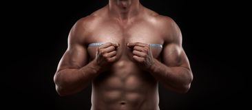 Bodybuilder with a measuring tape around his chest. Nude bodybuilder with a measuring tape around his chest isolated on black background Stock Image
