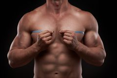 Bodybuilder with a measuring tape around his chest. Nude bodybuilder with a measuring tape around his chest isolated on black background Stock Photos