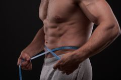 Bodybuilder with a measuring tape around his stomach. Nude bodybuilder with a blue measuring tape around his stomach isolated on black background royalty free stock photography