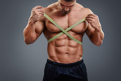Bodybuilder measuring waist with tape measure. Closeup of sports man measuring his waist with a tape measure. Bodybuilder with sexy six packs abs measures gain Stock Image