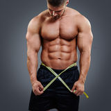 Bodybuilder measuring waist with tape measure. Fitness male model measuring his waist with tape measure isolated over gray background. Gain in abdominal muscles Stock Image