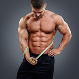 Bodybuilder measuring waist with tape measure. Muscular bodybuilder with perfect six pack abs looking down and holding tape measure. Gain in abdominal muscles Stock Photo